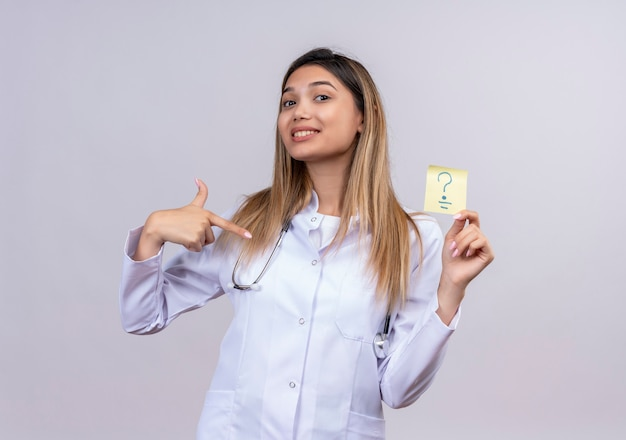 Молодая красивая женщина-врач в белом халате со стетоскопом держит бумагу для напоминания с вопросительным знаком, указывая указательным пальцем на нее положительно и счастливо