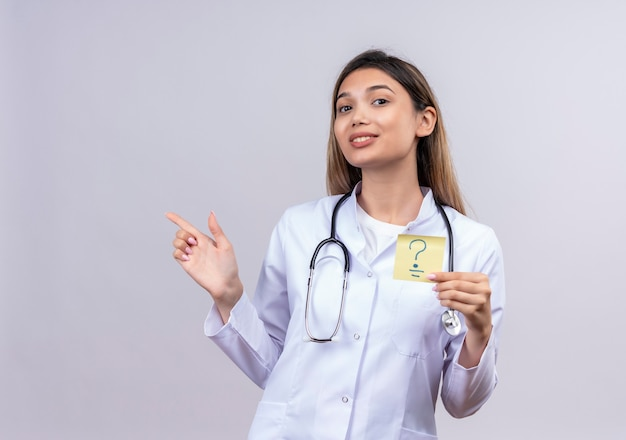 Young beautiful woman doctor wearing white coat with stethoscope holding reminder paper with question mark smiling cheerfully pointing with finger to the side