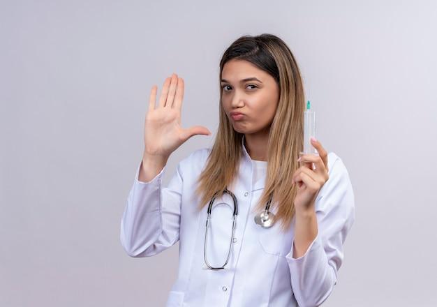 聴診器と注射器を保持している白いコートを着ている若い美しい女性医師は、一時停止の標識を作る開いた手で立って不快に見えます