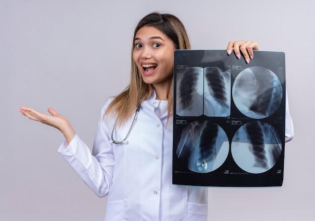 Молодая красивая женщина-врач в белом халате со стетоскопом, держащим рентген легких