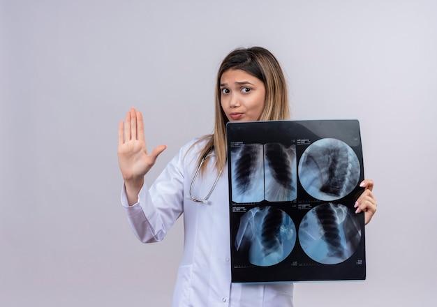 Молодая красивая женщина-врач в белом халате со стетоскопом, просверливающим рентгеновский снимок легких, делая знак остановки с открытой рукой с серьезным лицом с выражением страха