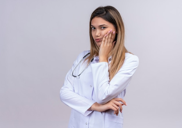 Young beautiful woman doctor wearing white coat with stethoscope looking bored with hand on chin waiting