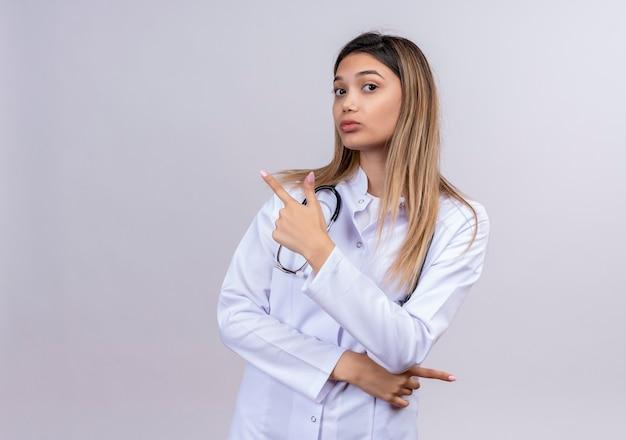 聴診器で白衣を着た若い美女医師が人差し指で後ろの何かを指差して自信を持って見える