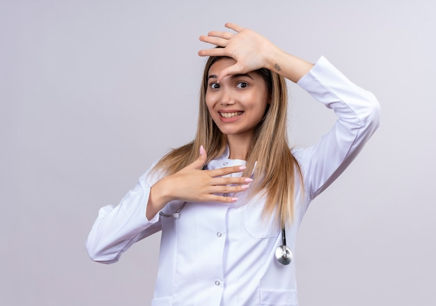 Молодая красивая женщина-врач в белом халате со стетоскопом выглядит смущенным, делая защитный жест с открытыми ладонями