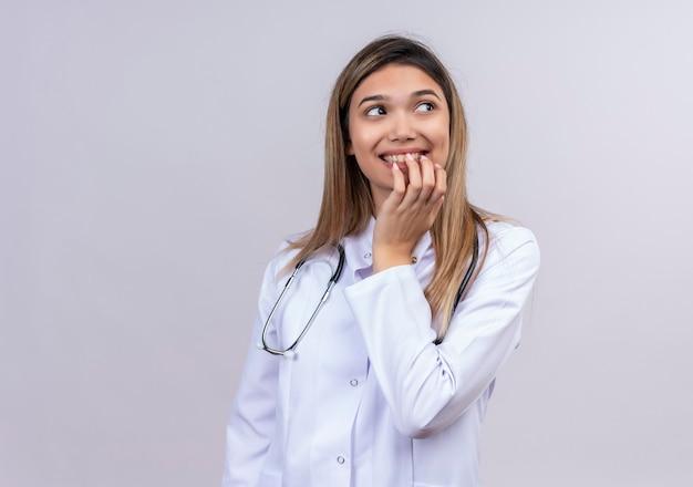 聴診器が終了し、驚きを待っている幸せな噛む爪と白衣を着ている若い美しい女性医師