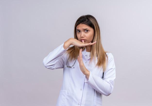 젊은 아름 다운 여자 의사 청진 기 흰색 코트를 입고 얼굴을 찡그린 얼굴로보고 손으로 시간 초과 제스처를 만들기