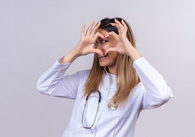 Giovane bella donna medico che indossa camice bianco con lo stetoscopio che fa gesto romantico del cuore con le dita che guardano attraverso questo segno che è adorabile