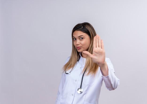 聴診器で白衣を着た若い美女医師が真面目な表情で真面目な顔で開いた手で一時停止の標識を作る
