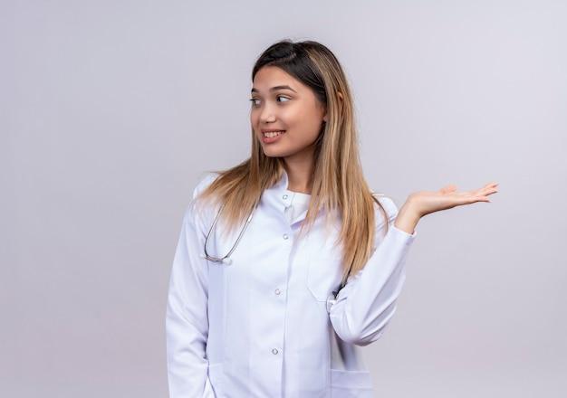 Giovane bella donna medico indossa camice bianco con lo stetoscopio che presenta un prodotto con la sua mano