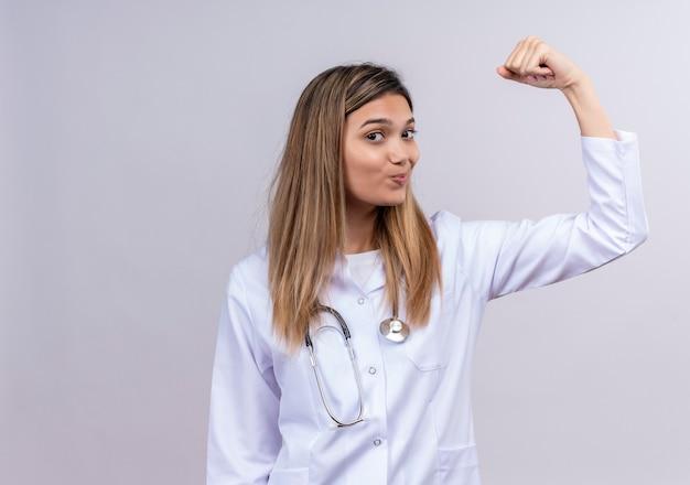 자신감이 웃는 승자처럼 팔뚝을 보여주는 주먹을 제기 청진기와 흰색 코트를 입고 젊은 아름 다운 여자 의사