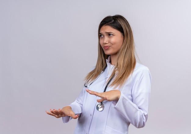 うんざりした表情で拒絶ジェスチャーで手のひらを上げる聴診器で白衣を着た若い美女医師