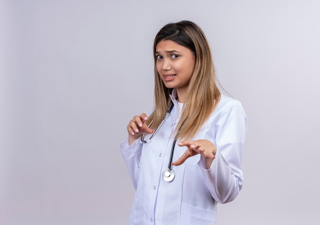 Young beautiful woman doctor wearing white coat with stethoscope raising palms in rejection gesture with disgusted expression