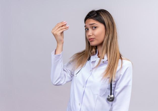Молодая красивая женщина-врач в белом халате со стетоскопом, потирающая палец, делая денежный жест рукой, прося денег