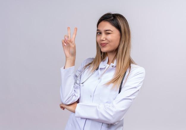 聴診器笑顔とウィンクで勝利のサインを示す白いコートを着ている若い美しい女性医師