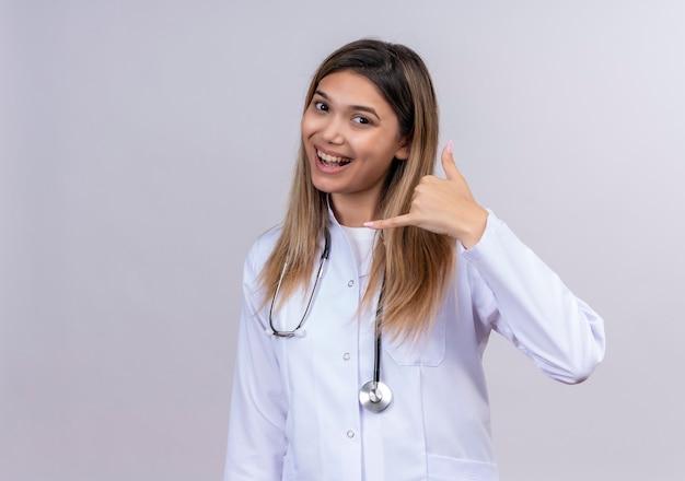 Giovane bella donna medico indossa camice bianco con lo stetoscopio sorridendo allegramente facendomi chiamare gesto