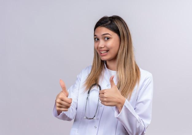 聴診器で白衣を着て元気に親指を見せて笑っている若い美しい女性医師