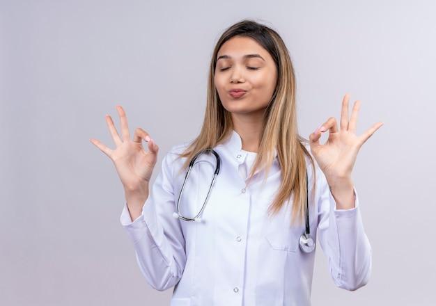目を閉じて立っている聴診器で白衣を着てリラックスして指で瞑想ジェスチャーを作る若い美しい女性医師