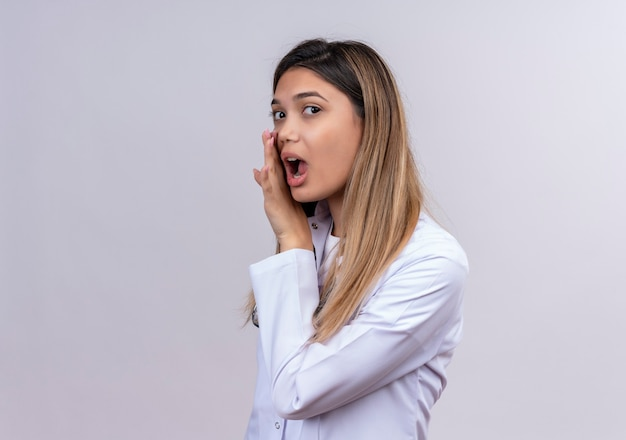 Young beautiful woman doctor wearing white coat with stethoscope telling a secret with hands near mouth