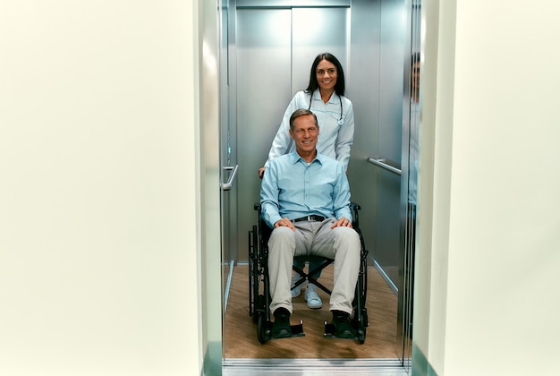 Young beautiful woman doctor with her disabled elderly patient in a wheelchair entered the elevator of a modern hospital.