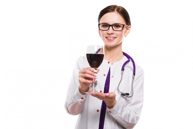 Young beautiful woman doctor with stethoscope offering wine in white uniform