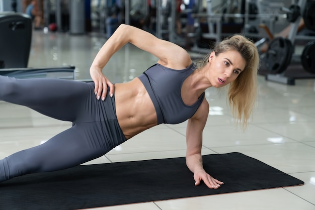 Young beautiful woman doing abdominal training at fitness club
