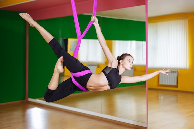 Young beautiful woman doing aerial yoga practice in purple hammock in fitness club.