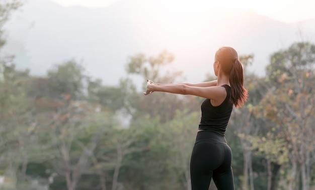 Молодая красивая женщина делает упражнения на открытом воздухе утром
