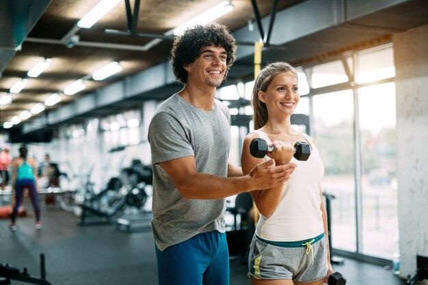 체육관에서 개인 트레이너와 함께 운동을 하는 젊은 아름다운 여성