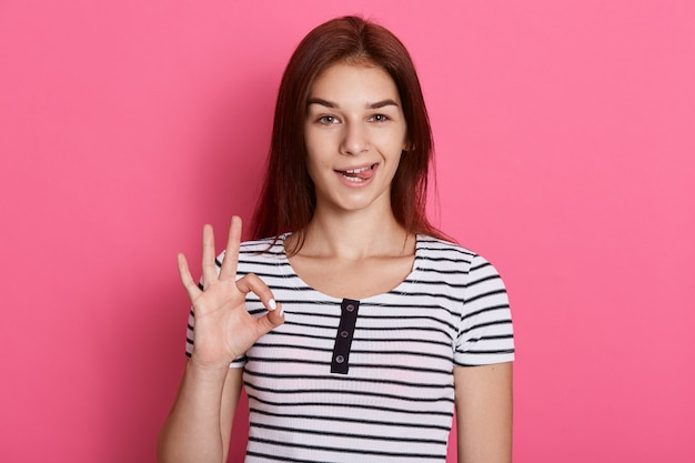 Young beautiful woman doing ok sign with fingers and showing her tounge,  with funny expression, posing isolated over pink wall.
