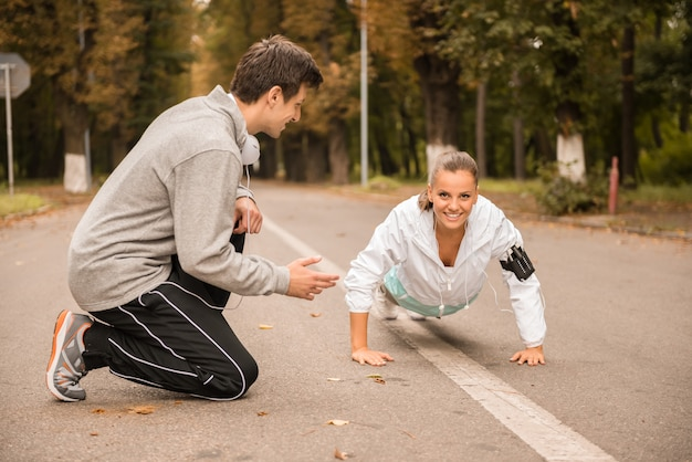 Young beautiful woman doing push ups with trainer outdoor.