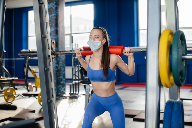 Young beautiful woman doing sports in the gym wearing a mask during the pandemic.