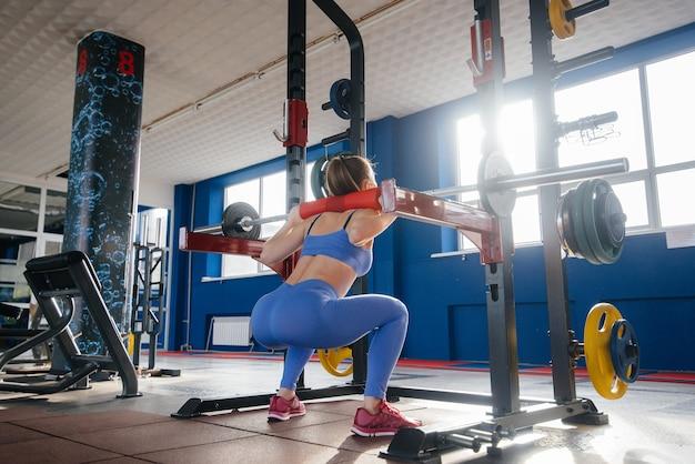 Молодая красивая женщина занимается спортом в тренажерном зале в маске во время пандемии.