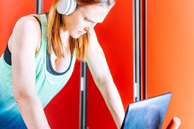 Молодая красивая женщина занимается спортом с музыкальными наушниками, глядя на экран ноутбука