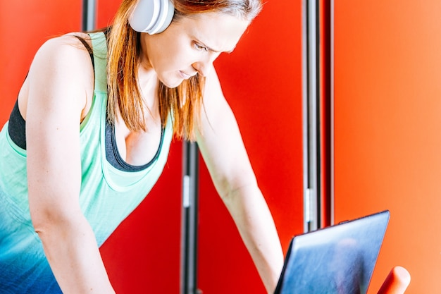 Young beautiful woman doing sports with music headphones looking at the screen of a laptop