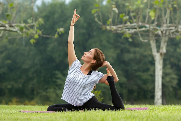 Young beautiful woman doing yoga exercise in green park. healthy lifestyle and fitness concept.