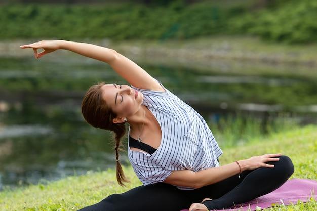 Giovane bella donna che fa esercizio di yoga nel parco verde. stile di vita sano e concetto di fitness.