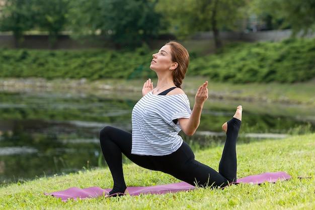 Giovane bella donna che fa esercizio di yoga nel parco verde