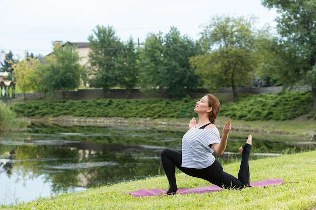 Young beautiful woman doing yoga exercise in green park