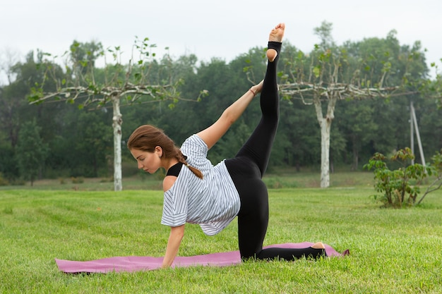 Молодая красивая женщина упражнения йоги в зеленом парке. концепция здорового образа жизни и фитнеса.
