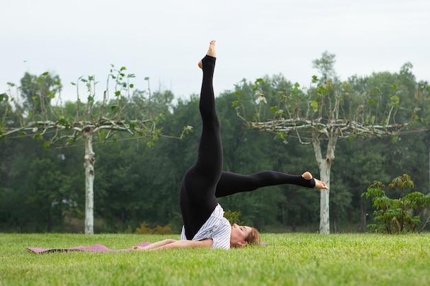 녹색 공원에서 요가 운동을 하 고 젊은 아름 다운 여자. 건강한 라이프 스타일과 피트니스 개념.