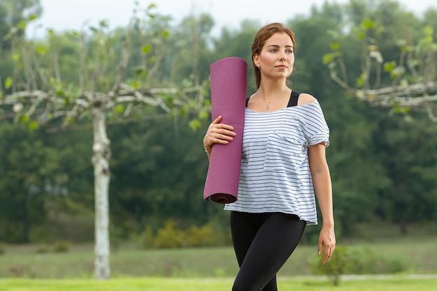 Молодая красивая женщина делает упражнения йоги в зеленом парке. концепция здорового образа жизни и фитнеса.