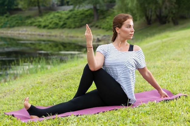 緑豊かな公園でヨガの練習をしている若い美しい女性。健康的なライフスタイルとフィットネスのコンセプト。