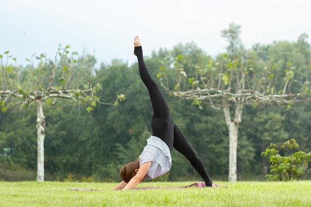 緑豊かな公園でヨガの練習を行う若い美しい女性