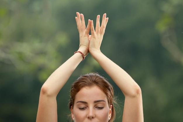 Молодая красивая женщина делает упражнения йоги в зеленом парке