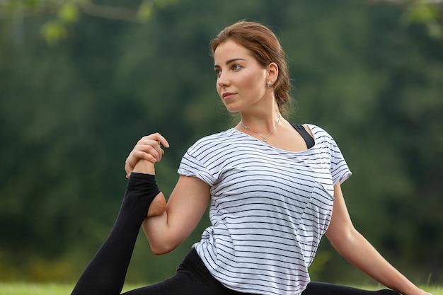 緑豊かな公園でヨガの練習をしている若い美しい女性