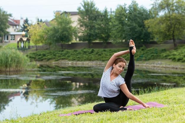 녹색 공원에서 요가 운동을 하 고 젊은 아름 다운 여자 무료 사진