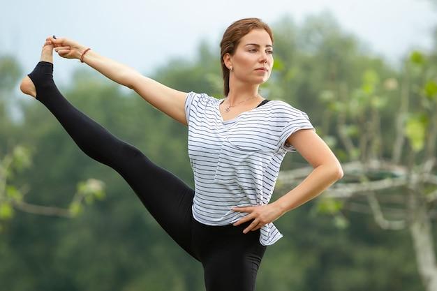 녹색 공원에서 요가 운동을 하 고 젊은 아름 다운 여자