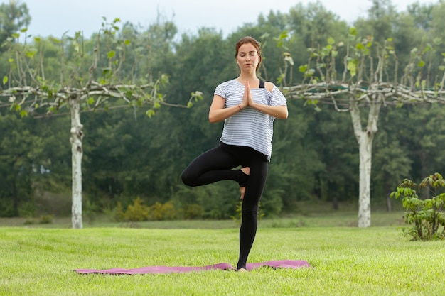 Young beautiful woman doing yoga exercise outdoors