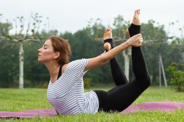 Молодая красивая женщина делает упражнения йоги на открытом воздухе