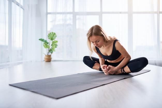 Молодая красивая женщина, занимаясь йогой в современной светлой комнате с большими окнами. йога на дому концепции.